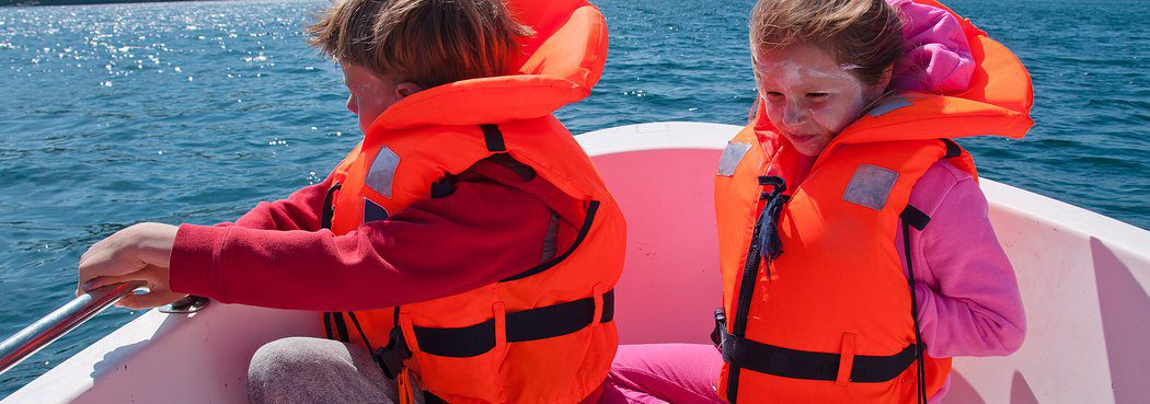 two kids wearing life jackets in water