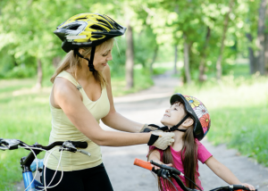 mom putting bicycle helmet on kid